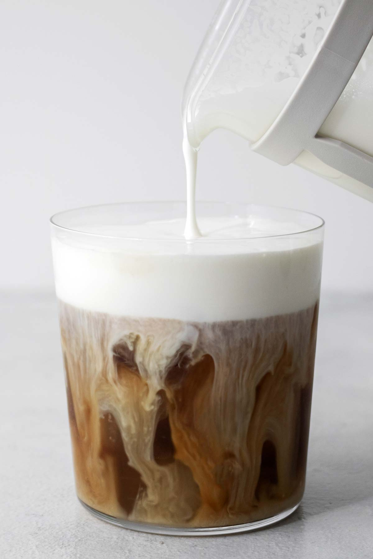 Pouring cold foam into a cup of iced coffee.